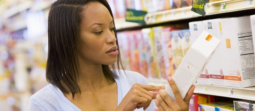 woman checking back of a cereal at a grocery store