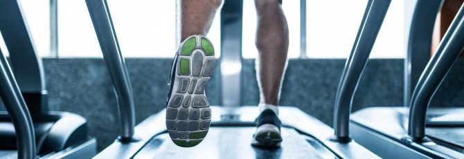 Legs of sportsman running on treadmill: sport and healthy lifestyle concept