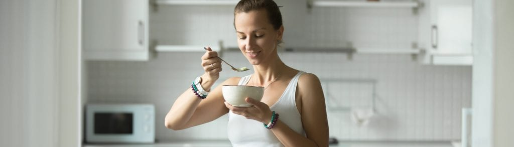 woman in kitchen eating out of a bowl with a spoon