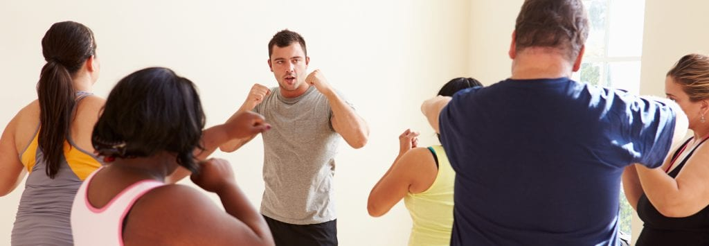 man teaching fitness class to other people