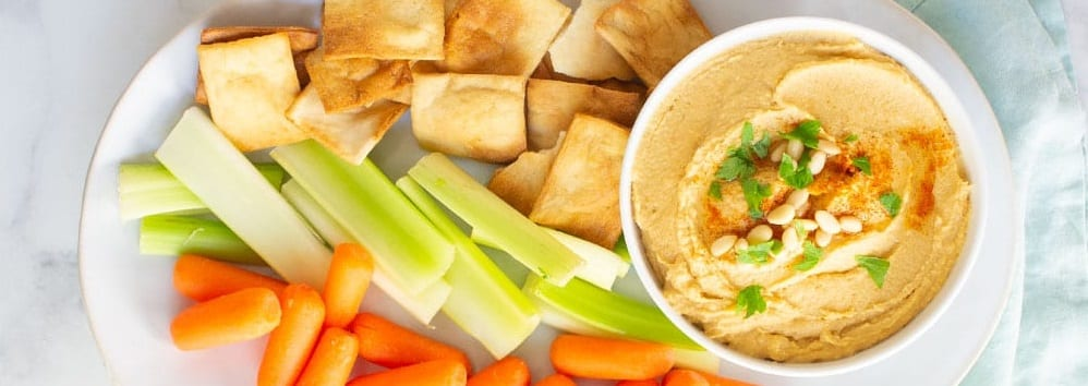 hummus in a bowl next to carrots, celery, and crackers