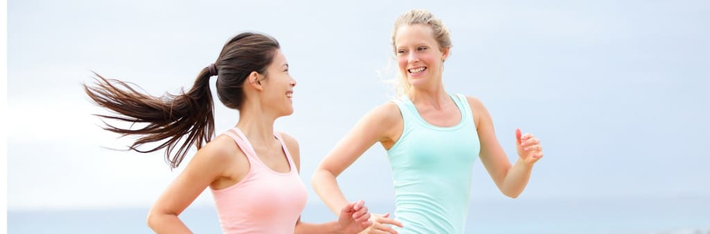 two woman on a jog looking at each other smiling
