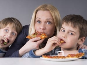 Hungry family, mother and son eating pizza, younger kid prefers