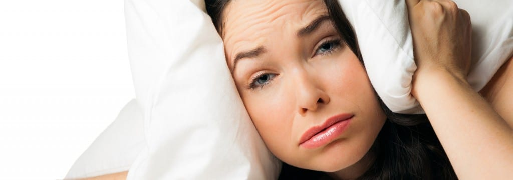 woman holding pillow around her head and blowing air out of her mouth as if stressed
