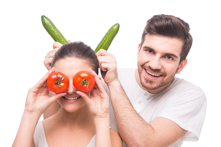 Cheerful young couple with vegetables tomatoes and cucumbers on the white background.