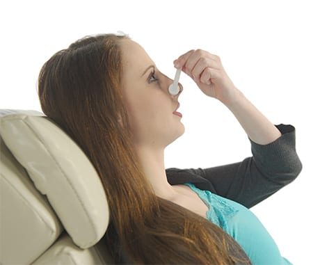woman sitting in chair plugging nose with nose clamps