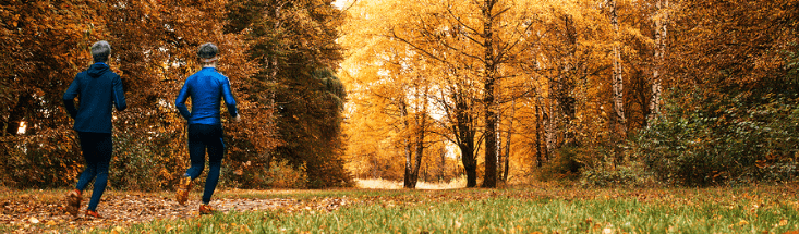 two men running by trees in the fall