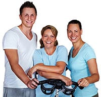 a man and two women standing behind an exercise bike smiling