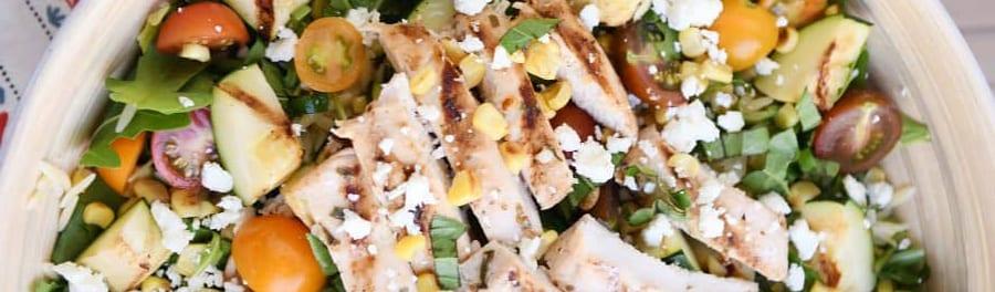 grilled chicken salad in wooden bowl