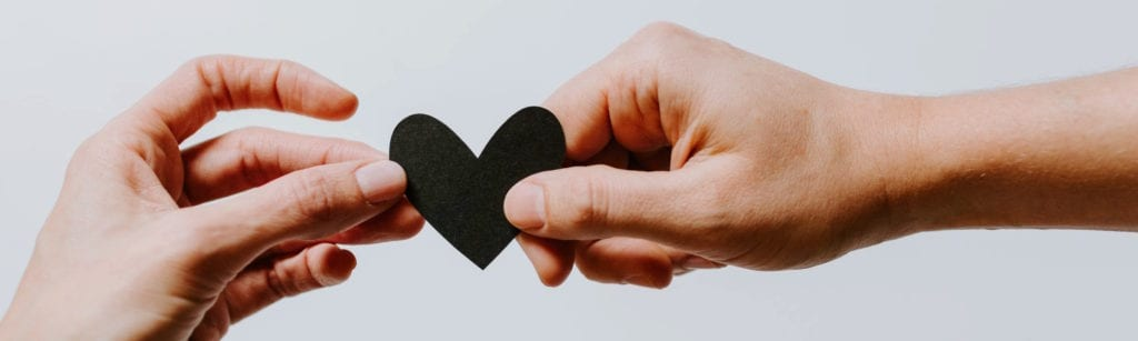 one hand passing on a black paper heart to another hand