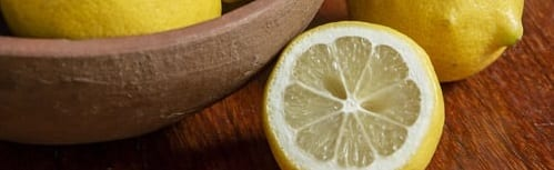 whole lemon in clay bowl. whole and half lemon outside of bowl on wooden table