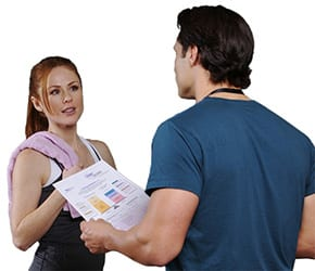 woman with towel over shoulder being coached by a male fitness instructor